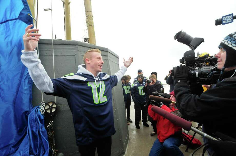 """Seattle rapper Macklemore, whose single """"Thrift Shop"""" just went platinum, throws his arms wide as he predicts that the Seahawks will win this Sunday. He was on the Space Needle roof Friday to help raise the 12th man flag.  Photo: LINDSEY WASSON, Seattlepi.com / SEATTLEPI.COM"""
