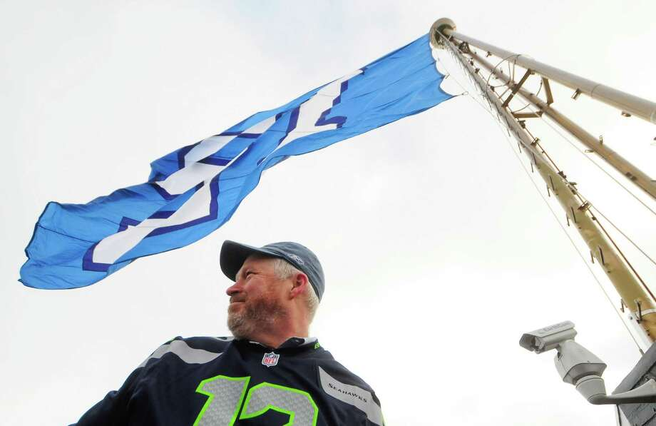 Seattle Mayor Mike McGinn stands under the 12th man flag after it was raised on the Space Needle on Friday.  Photo: LINDSEY WASSON, Seattlepi.com / SEATTLEPI.COM