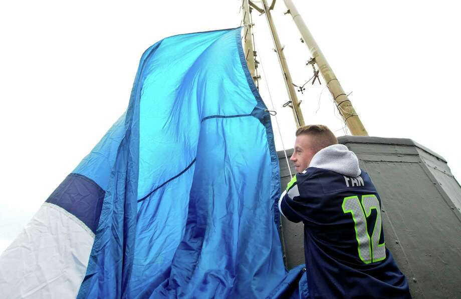 Macklemore helps raise the 12th man flag.  Photo: LINDSEY WASSON, Seattlepi.com / SEATTLEPI.COM