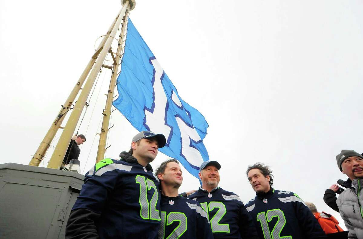 From left: Ben Gibbard and Nick Harmer of Death Cab for Cutie, Mayor Mike McGinn and Jason Finn of the Presidents of the United States of America stand on the Space Needle roof on Friday after the 12th man flag was raised to honor the Seahawks. The team will face Washington Redskins in a playoff game Sunday.