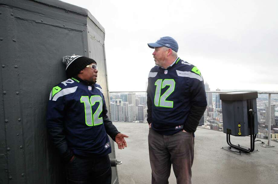 Tendai 'Baba' Maraire of Shabazz Palaces and Mayor Mike McGinn chat on the Space Needle roof, where the Seahawks' 12th man flag was raised Friday. (Photo by Lindsey Wasson) Photo: LINDSEY WASSON, Seattlepi.com / SEATTLEPI.COM