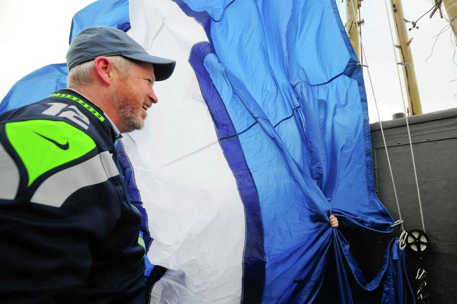 Mayor Mike McGinn laughs as Space Needle staff try to keep the 12th man flag from unfurling Friday.   Photo: LINDSEY WASSON, Seattlepi.com / SEATTLEPI.COM