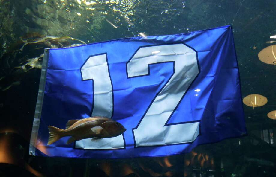 "A fish swims past a ""12th Man"" flag at the Seattle Aquarium on Friday. (AP Photo/Ted S. Warren) Photo: Associated Press"