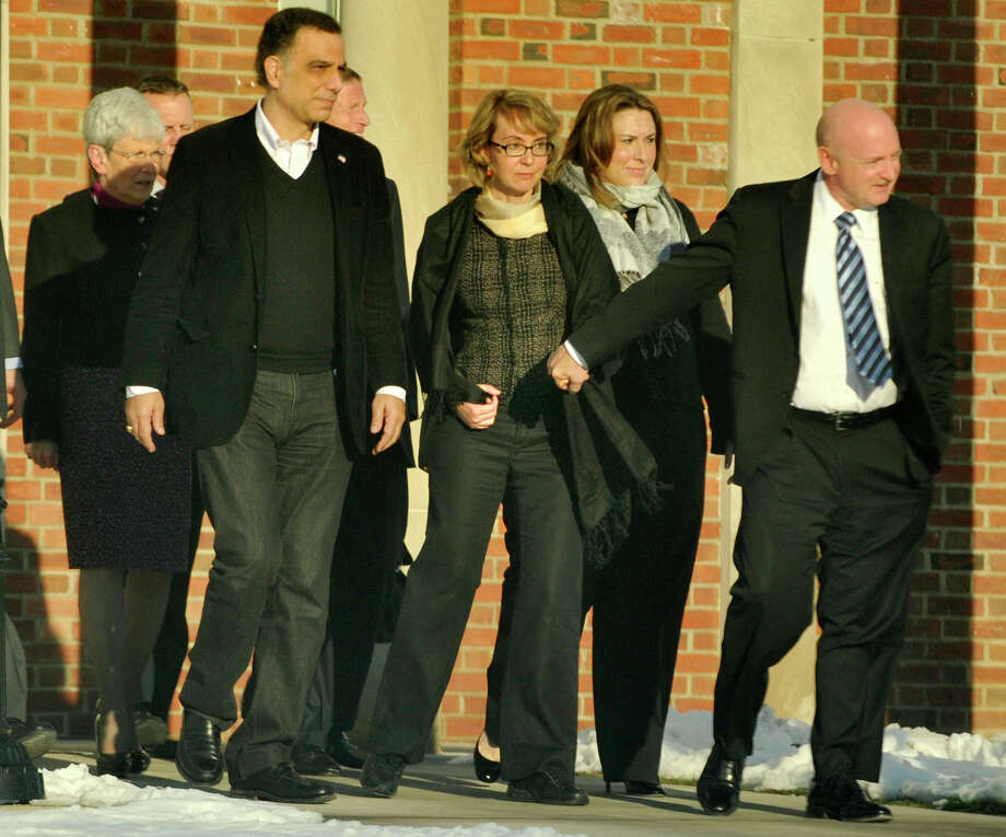 Former Congresswoman Gabrielle Giffords, center, holds hands with her husband, Mark Kelly, while exiting Newtown Town Hall at Fairfield Hills Campus after meeting with Newtown First Selectman Pat Llodra and other officials on Friday, Jan. 4, 2013. Photo: Jason Rearick / The News-Times