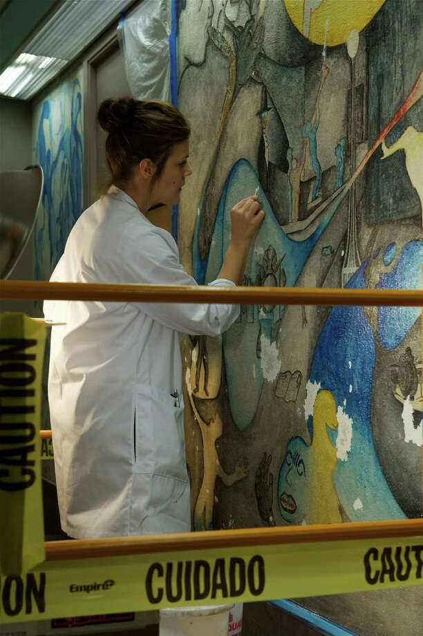 Nicole Seguin of Evergreen Architectural Arts performs the tedious work of restoring one of the murals on display at Texas Southern University. Implemented by Dr. John T. Biggerss and created by graduating art students, the murals give a visual narrative of African American culture with generational specific themes. Photo: Earlie Hudnall