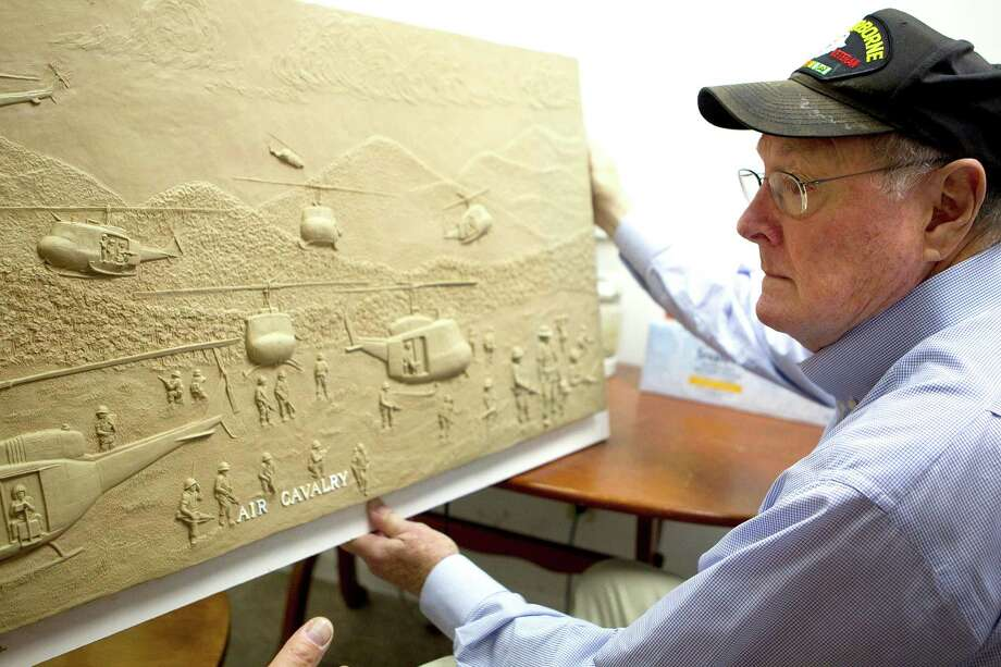 Vietnam veteran and chairman for the Texas Capitol Vietnam Veterans Monument looks at a panel sculpted in clay by sculptor Duke Sundt that will be part of the base of the monument at the Deep in the Heart Art Foundry  Wednesday, Nov. 7, 2012, in Bastrop. 