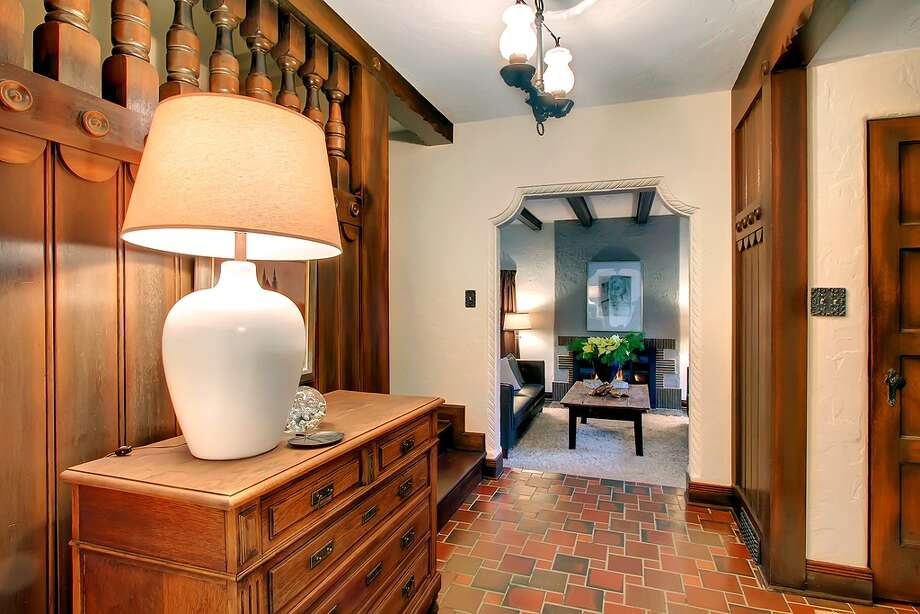 Entry of 321 36th Ave. E. The 3,250-square-foot house, built in 1931, has four bedrooms, 3.25 bathrooms, tons of dark-stained wood, beamed ceilings, French doors, leaded glass, skylights, a lower-level nanny quarters with a fireplace and kitchen, and a terraced yard with two patios on a 5,799-square-foot lot. It's listed for $1.195 million. Photo: Courtesy Michael Ravenscroft/Windermere Real Estate
