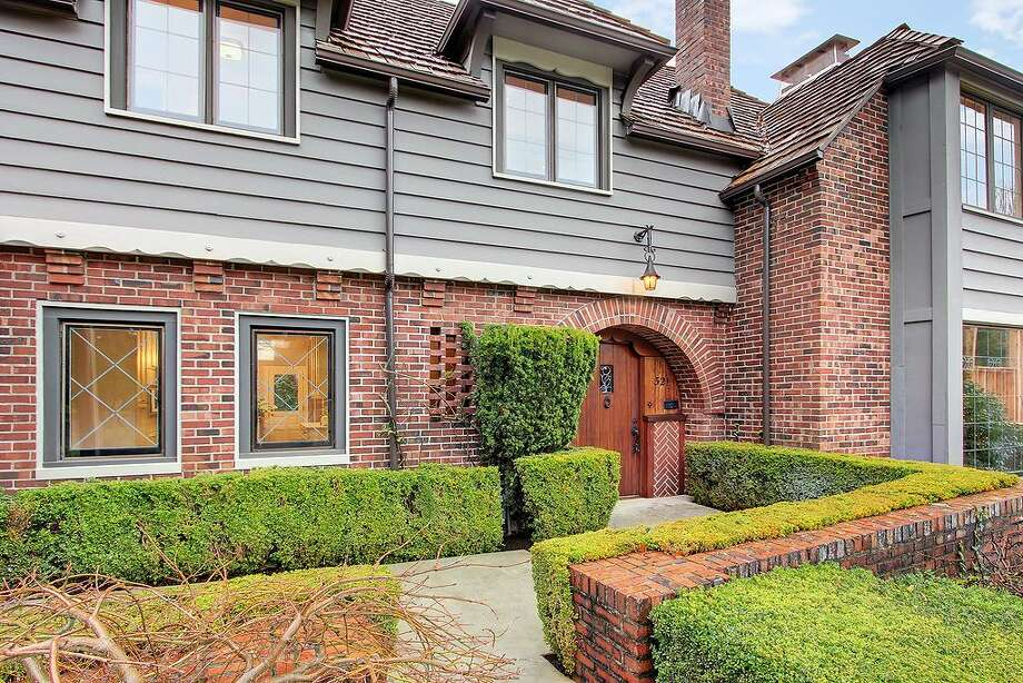 Front of 321 36th Ave. E. The 3,250-square-foot house, built in 1931, has four bedrooms, 3.25 bathrooms, tons of dark-stained wood, beamed ceilings, French doors, leaded glass, skylights, a lower-level nanny quarters with a fireplace and kitchen, and a terraced yard with two patios on a 5,799-square-foot lot. It's listed for $1.195 million. Photo: Courtesy Michael Ravenscroft/Windermere Real Estate