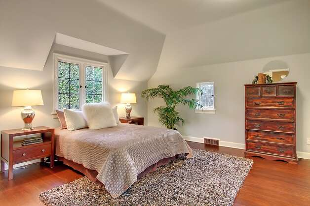 Master bedroom of 321 36th Ave. E. The 3,250-square-foot house, built in 1931, has four bedrooms, 3.25 bathrooms, tons of dark-stained wood, beamed ceilings, French doors, leaded glass, skylights, a lower-level nanny quarters with a fireplace and kitchen, and a terraced yard with two patios on a 5,799-square-foot lot. It's listed for $1.195 million. Photo: Courtesy Michael Ravenscroft/Windermere Real Estate
