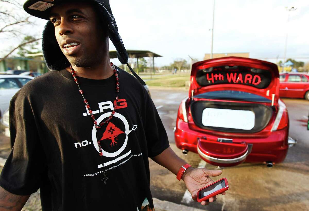 King Fish jokes with on lookers as he represents 4th Ward with his car, a five wheel slab painted red to represent his team, Wednesday, Dec. 19, 2012, at Cloverland Park in Houston. Teams are made up of people from certain neighborhoods. King Fish says he buys and fixes up cars for people in his neighborhood. ( Nick de la Torre / Houston Chronicle )