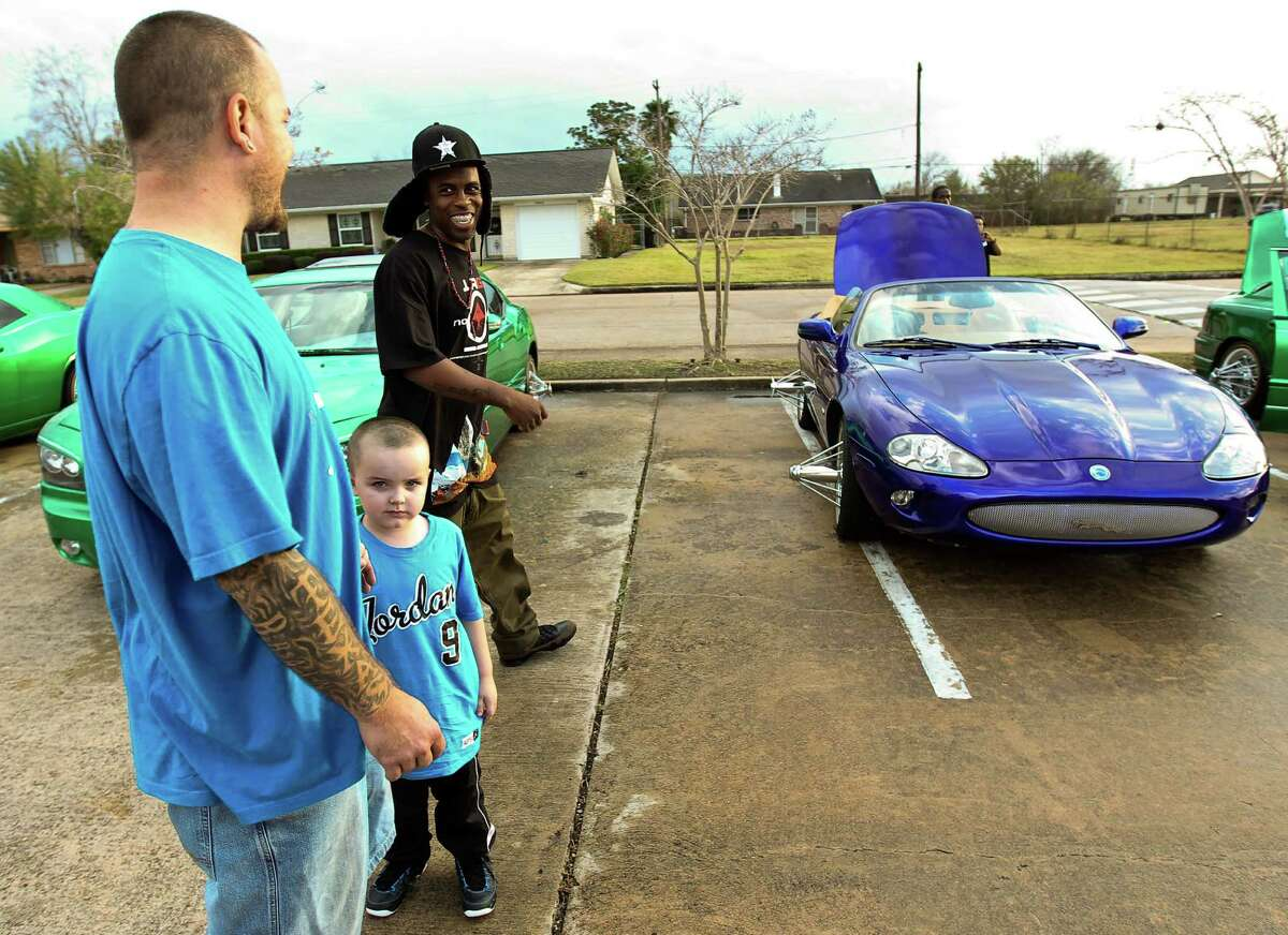 King Fish, facing, has a word with B.G. Porter, with his son B.G. Porter Jr., , Wednesday, Dec. 19, 2012, in Houston. Porter, who owns a body shop, explains how he made a custom grill on his Jaguar and that he painted it Baka Blue. Baka blue is a tribute to a man wit the last name Baka who died recently. ( Nick de la Torre / Houston Chronicle )