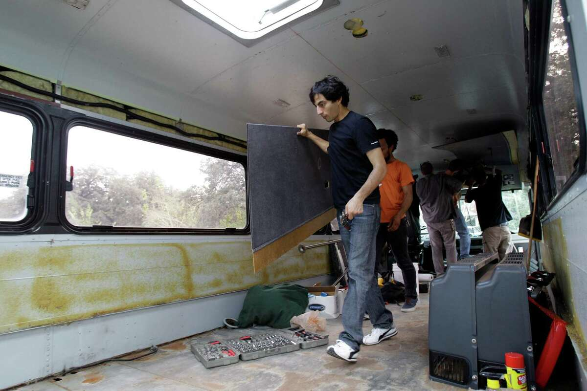 Ali Naghdali, left, and Jonathan Jackson, second from left, are among the volunteers working on the bus.