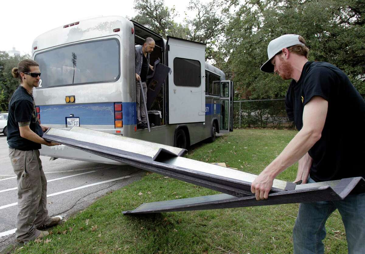 Volunteers Eric Du Bruin, left, and Austin Owen, right, both of Dallas help Rice University art professor Christopher Sperandio, center, with transforming an old university shuttle bus into a traveling camper for artists Saturday, Dec. 15, 2012, in Houston. ( Melissa Phillip / Houston Chronicle )