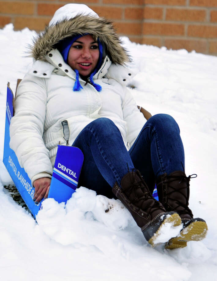 Angelo State student Briana Martinez sleds down the hill in front of the Junell Center, Friday, Jan. 4, 2013. Martinez and her friend Sydni Barr came out with their dogs, Buck and Tazz, to play in the snow before it melted. This is San Angelo's first seasonal snowfall. About 2.8 inches of snow had fallen by Friday morning. Photo: Kimberley Meyer, Associated Press / San Angelo Standard-Times