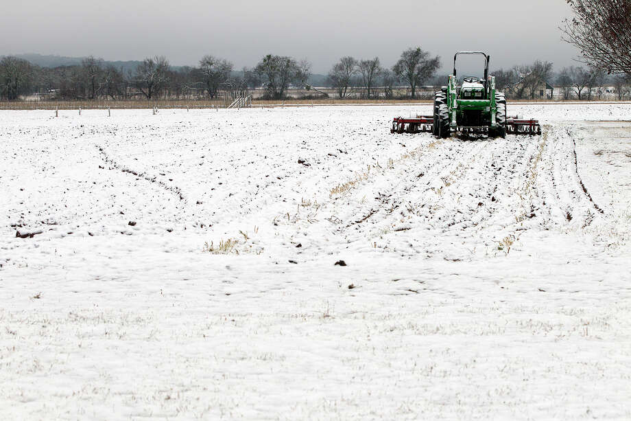 Snow fell in the Hill Country just west of Stonewall, Texas Friday, Jan. 4, 2013, where this tractor sits ready for plowing, covering peach orchards and grape fields in a thin layer of white. Photo: Alberto Martinez, Associated Press / Austin American-Statesman