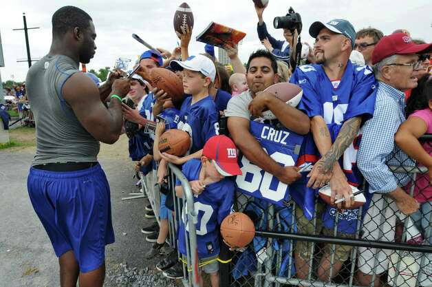 New York Giants defensive end Justin Tuck signs autographs at the end of practice on the last day of training camp at UAlbany on Tuesday Aug. 14, 2012 in Albany, N.Y.  (Philip Kamrass / Times Union archive) Photo: Philip Kamrass / 00018767C