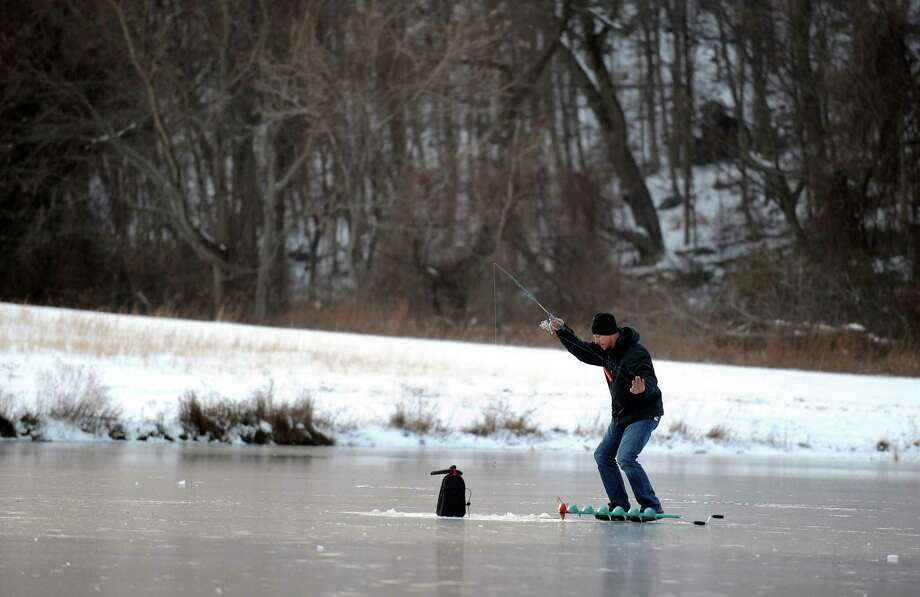 Ryan Adams, of Derby, ices fishes on Pickett's Pond at Osbornedale State Park in Derby, Conn. Friday, Jan. 4, 2013. Adams, an Algebra teacher, said the ice was about 4 inches thick across the pond. Photo: Autumn Driscoll / Connecticut Post