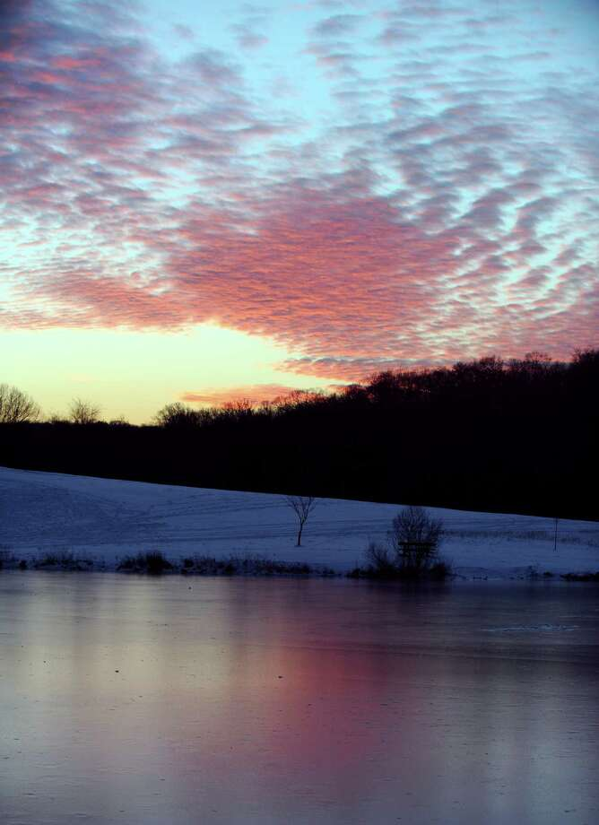 The sun sets over a frozen Pickett's Pond at Osbornedale State Park in Derby, Conn. Friday, Jan. 4, 2013. Photo: Autumn Driscoll / Connecticut Post
