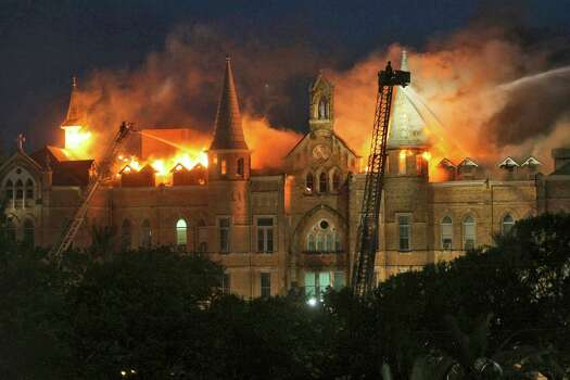 In this May 6, 2008 file photo San Antonio firefighters spray water on the roof of the main building of Our Lady of The Lake University during a multiple alarm fire in San Antonio. One year after the biggest San Antonio fire in a decade engulfed the Gothic-style main building at the small Catholic school that had been struggling to stay open is in now flourishing amid a remarkable turnaround, thanks, in part, to the blaze. (AP Photo/San Antonio Express-News, William Luther, File) *** SAN ANTONIO OUT, NO SALES, MAGS OUT *** Photo: William Luther, Express-News / San Antonio Express-News