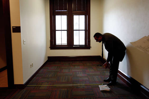 Michael Alvarado, account representative, measures space for furniture on the fourth floor of Our Lady of the Lake University Main Building, Nov. 11, 2010. JERRY LARA/glara@express-news.net Photo: JERRY LARA, Express-News / glara@express-news.net