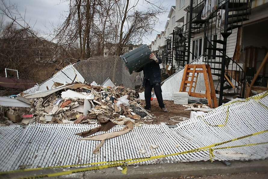 A laborer empties debris from a home damaged by Superstorm Sandy in the Midland Beach area of Staten