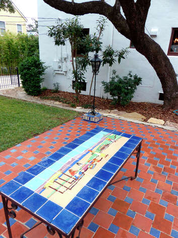 A table in the backyard features tile work that is irreplaceable. Photo: Billy Calzada, San Antonio Express-News / SAN ANTONIO EXPRESS-NEWS