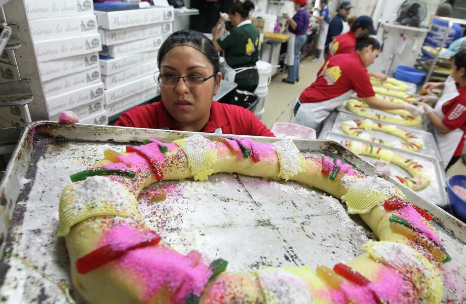 Claudia Vasquez slides 'Roscas de Reyes' or Kings Bread on top a rack of breads ready to be baked at El Bolillo Bakery in preparation for the Epiphany celebration over the weekend. El Bolillo Bakery is baking over 5,000 roscas this year. Photo: Mayra Beltran, Houston Chronicle / © 2012 Houston Chronicle