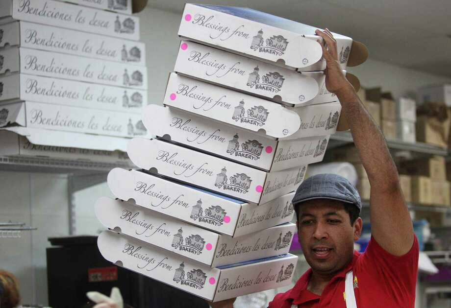 Daniel Santiago carries the decorative boxes for the 'Roscas de Reyes' or Kings Bread at El Bolillo Bakery in preparation for the Epiphany celebration over the weekend on Friday, Jan. 4, 2013, in Houston. Photo: Mayra Beltran, Houston Chronicle / © 2012 Houston Chronicle