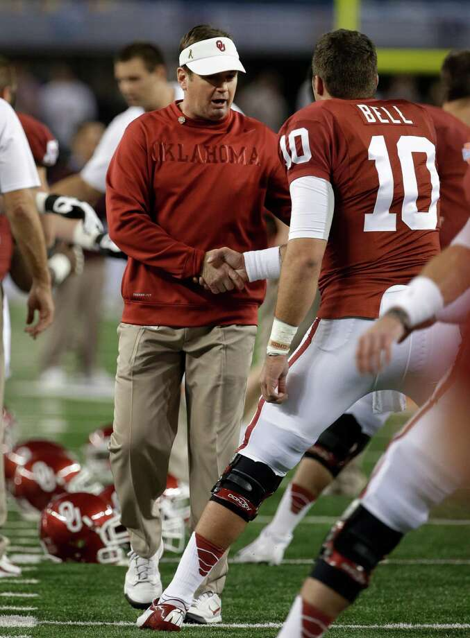 Oklahoma coach Bob Stoops shakes hands with quarterback Blake Bell (10) as the team stretches before the Cotton Bowl NCAA college football game against Texas A&M on Friday, Jan. 4, 2013, in Arlington, Texas. (AP Photo/Tony Gutierrez) Photo: Tony Gutierrez, Associated Press / AP