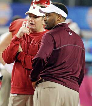 Oklahoma Sooners head coach Bob Stoops (left) and Texas A&M Aggies head coach Kevin Sumlin talk before the 77th AT&T Cotton Bowl Classic with the Friday Jan. 4, 2013 at Cowboys Stadium in Arlington, Tx. Photo: Edward A. Ornelas, Express-News / © 2012 San Antonio Express-News