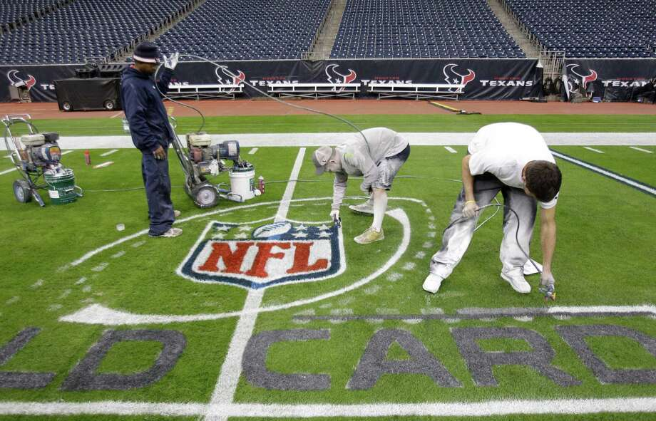 Grounds crew members Craig Merritt, left, manager Brandon Smith, center, and Daniel Ryan, right, work to paint the NFL playoff logo onto the football field at Reliant Stadium Friday, Jan. 4, 2013, in Houston. The Houston Texans will face the Cincinnati Bengals in a AFC Wild Card playoff game on Saturday.  It takes 8 to 10 hours to complete the paint job on the entire field, using 150 gallons of water based paint. Photo: Melissa Phillip, Houston Chronicle / © 2012 Houston Chronicle