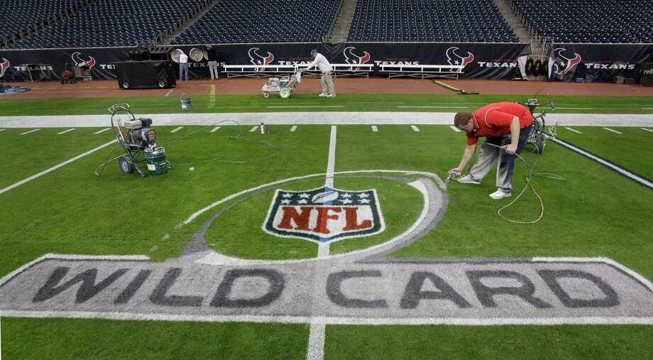 Grounds crew members Andy Hollister, left, and Jared Davis, right, work to paint the NFL football field at Reliant Stadium Friday, Jan. 4, 2013, in Houston. Photo: Melissa Phillip, Houston Chronicle / © 2012 Houston Chronicle