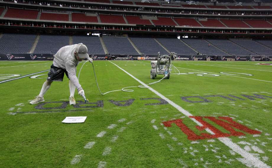Grounds manager Brandon Smith paints the NFL playoff logo onto the football field at Reliant Stadium. Photo: Melissa Phillip, Houston Chronicle / © 2012 Houston Chronicle