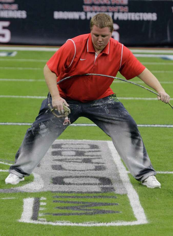 Grounds crew member Jared Davis paints a NFL playoff logo onto the football field at Reliant Stadium. Photo: Melissa Phillip, Houston Chronicle / © 2012 Houston Chronicle