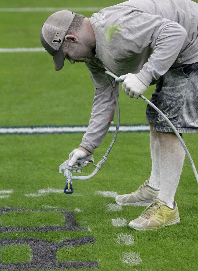 Covered in white paint, grounds manager Brandon Smith and his crew paint the NFL football field at Reliant Stadium. Photo: Melissa Phillip, Houston Chronicle / © 2012 Houston Chronicle