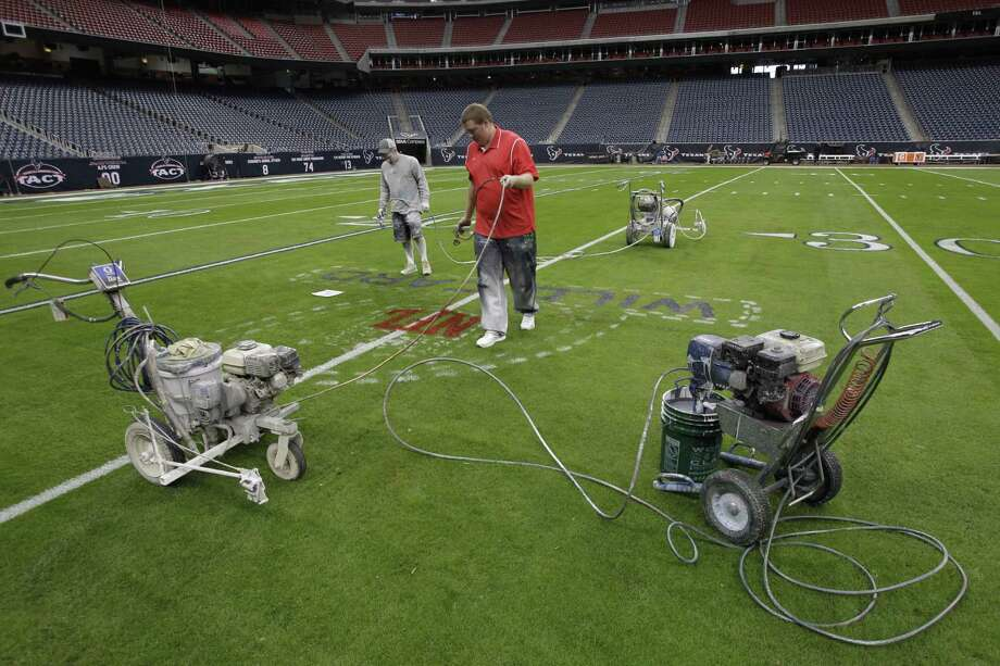 Grounds manager Brandon Smith, left, and crew member Jared Davis right, paint the NFL playoff logo onto the football field at Reliant Stadium. Photo: Melissa Phillip, Houston Chronicle / © 2012 Houston Chronicle
