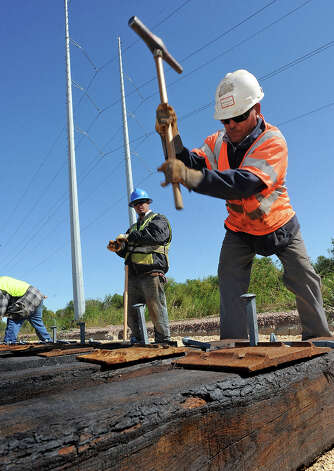 Workers construct one of several rail lines that will navigate the soon to be OmniPort in Port Arthur. Privately funded, the $95 terminal based in Port Arthur is expected to generate more business and jobs while improving transportation ways in Southeast Texas.  Photo taken Thursday, November 10, 2010 Guiseppe Barranco/The Enterprise Photo: Guiseppe Barranco, STAFF PHOTOGRAPHER / The Beaumont Enterprise