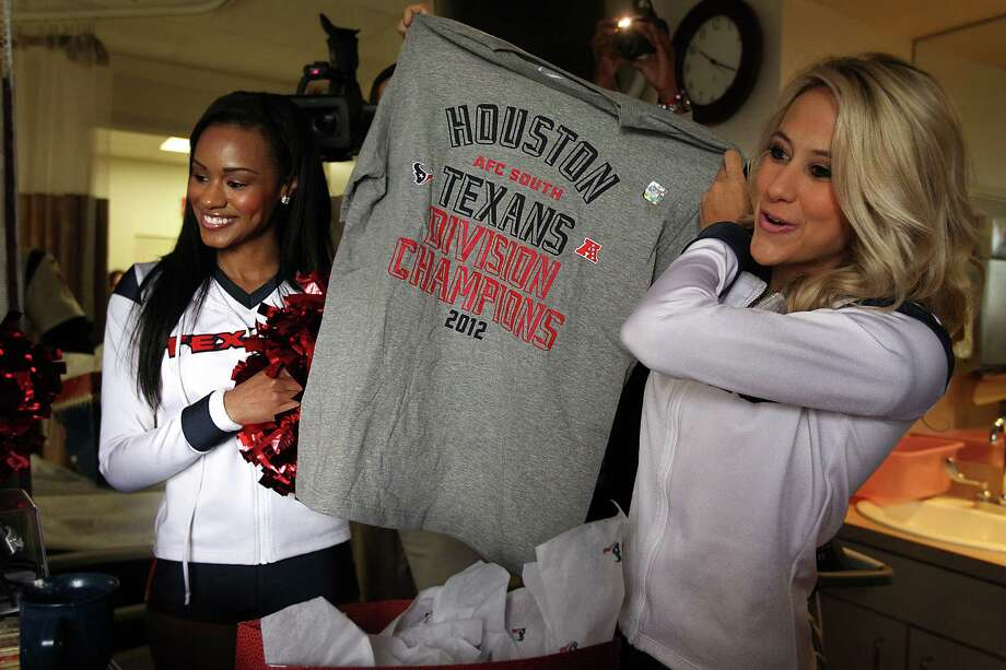 Texans cheerleaders Brittany, left, and Lauren L. show patients a gift from the Texans during a visit at Methodist Outpatient Center on Thursday. Lauren L. was voted the NFL's most beautiful cheerleader. Photo: Mayra Beltran, Houston Chronicle / © 2012 Houston Chronicle