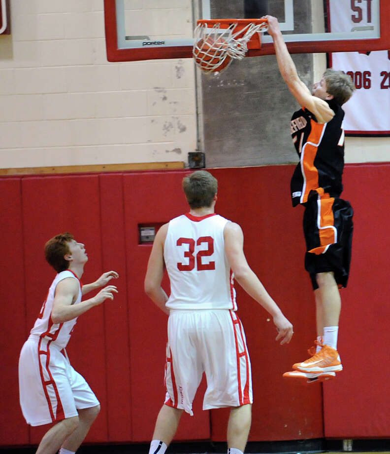 At right, Kurt Steidl of Ridgefield dunks the ball on a second quarter alley-oop play as Alex Wolf # 32 of Greenwich and teammate Jake Tennenbaum, left,  looks on during the boys high school basketball game between Greenwich and Ridgefield at Greenwich High School, Friday night, Jan. 4, 2013. Photo: Bob Luckey / Greenwich Time