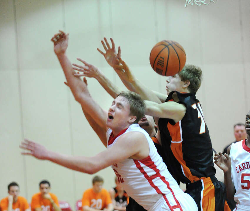 At left, Alex Wolf # 32 of Greenwich goes for an offensive rebound during the boys high school basketball game between Greenwich and Ridgefield at Greenwich High School, Friday night, Jan. 4, 2013.