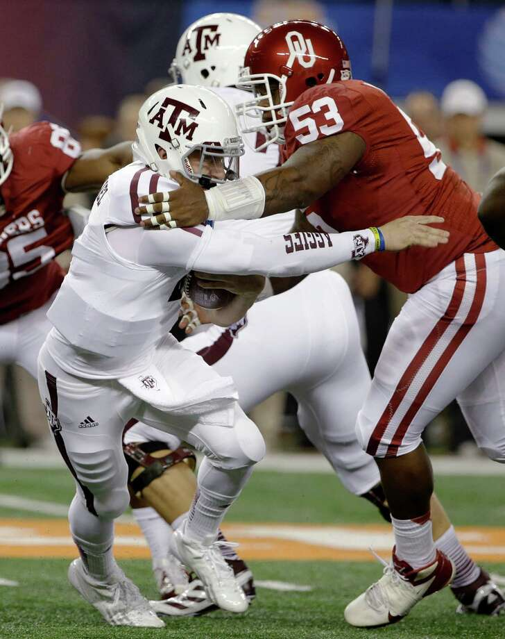 Texas A&M's Johnny Manziel escapes a tackle attempt by Oklahoma's Casey Walker (53) behind the line of scrimmage in the first half of the Cotton Bowl NCAA college football game Friday, Jan. 4, 2013, in Arlington, Texas. (AP Photo/Tony Gutierrez) Photo: Tony Gutierrez, Associated Press / AP