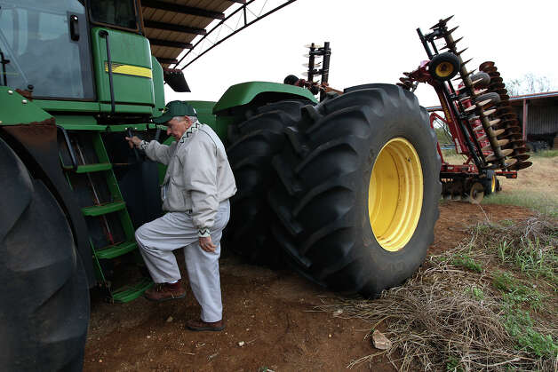 Jack Chiodo steps off his tractor near Dilley. The farmer is one of those finding relief in estate tax provisions that were part of the so-called fiscal cliff bill that Congress passed last week. Photo: Kin Man Hui, San Antonio Express-News / © 2012 San Antonio Express-News