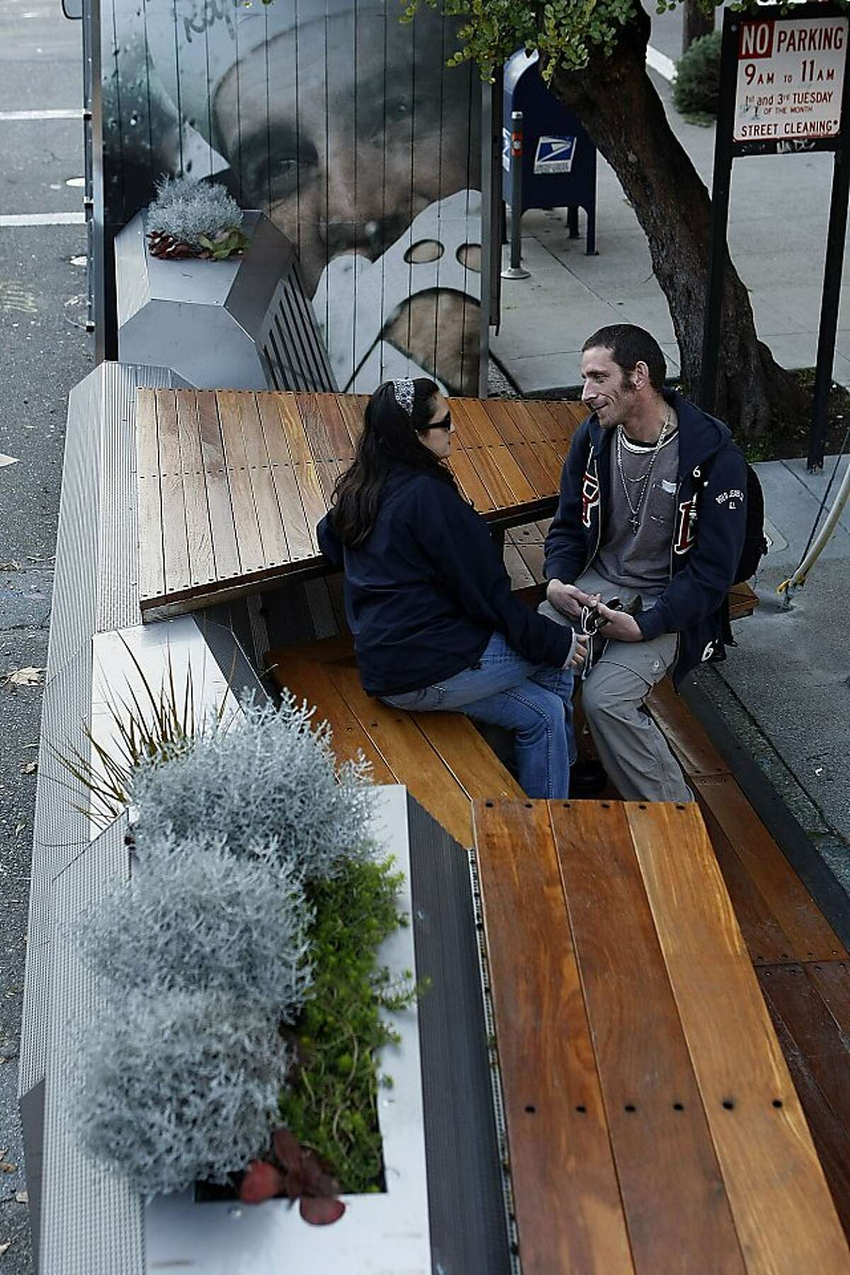 Isabella Baker talks to Jonathon Rocket, both from New York, at the new parklet outside Rapha Cycle Club on January 3, 2013 in San Francisco, Calif. The parklet, which is at the intersection of Filbert Street and Filmore Street, is built from a bicycle truck that was split and had seats added to the middle for the public to utilize.