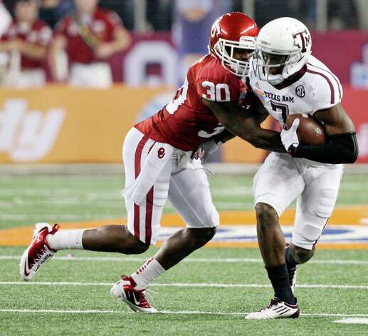 Texas A&M Aggies' Uzoma Nwachukwu tries to shake the tackle of Oklahoma Sooners' Javon Harris during first half action of the 77th AT&T Cotton Bowl Classic held Friday Jan. 4, 2013 at Cowboys Stadium in Arlington, Tx. Photo: Edward A. Ornelas, Express-News / © 2012 San Antonio Express-News
