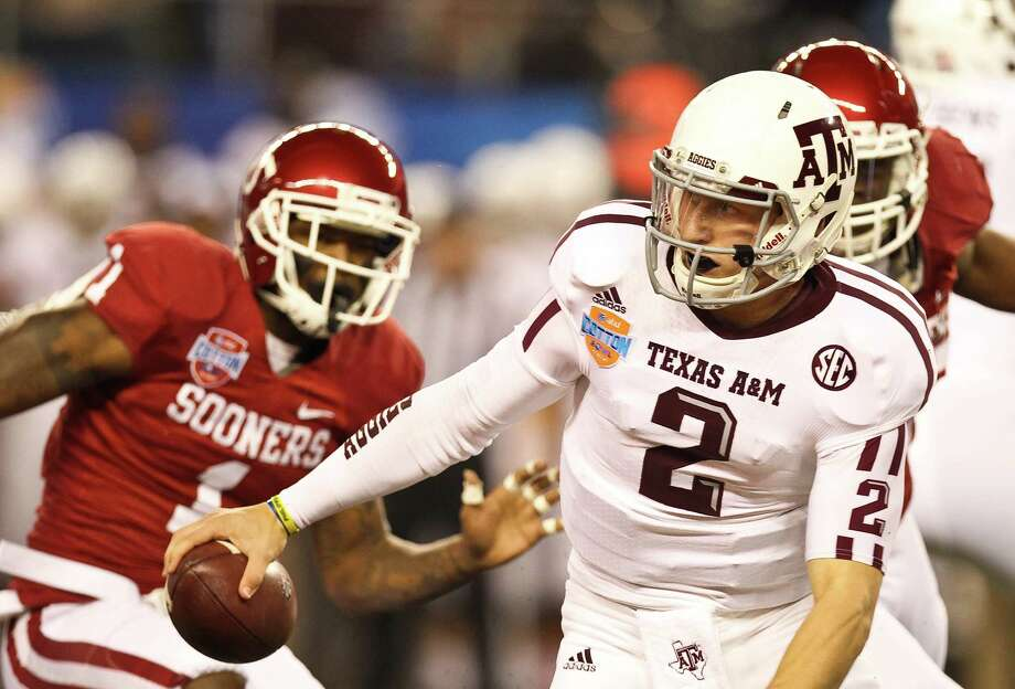 Texas A&M quarterback Johnny Manziel (2) scrambles from Oklahoma defensive back Tony Jefferson (1) for a first down during the first quarter of the Cotton Bowl college football game, Friday, Jan. 4, 2013, in Cowboys Stadium in Arlington. Photo: Nick De La Torre, Houston Chronicle / © 2013  Houston Chronicle