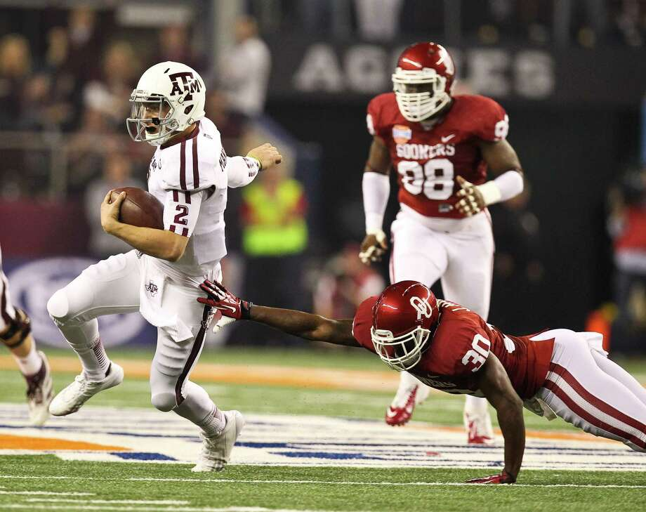 Texas A&M quarterback Johnny Manziel (2) gets past Oklahoma defensive back Javon Harris (30) and the rest of the Sooner defense for a first down during the second quarter of the Cotton Bowl college football game, Friday, Jan. 4, 2013, in Cowboys Stadium in Arlington. Photo: Nick De La Torre, Houston Chronicle / © 2013  Houston Chronicle