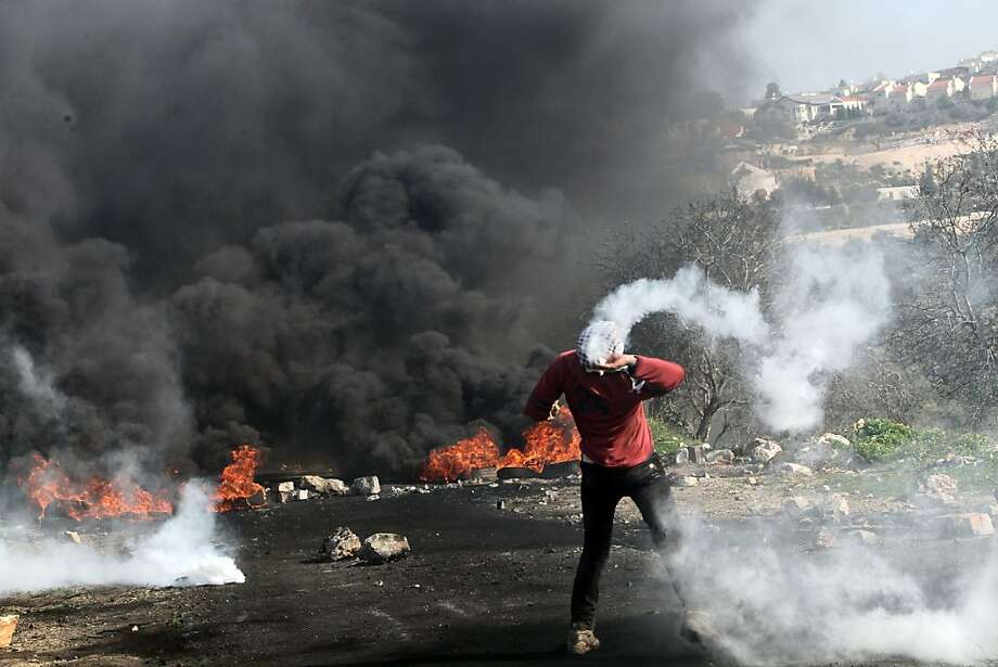 A Palestinian protester throws back a tear gas canister fired by Israeli soldiers near a cloud of black smoke rising from burning tyres during a demonstration against the expropriation of Palestinian land by Israel in the village of Kfar Qaddum, near the occupied West Bank city of Nablus, on January 4, 2013. Photo: Jaafar Ashtiyeh, AFP/Getty Images