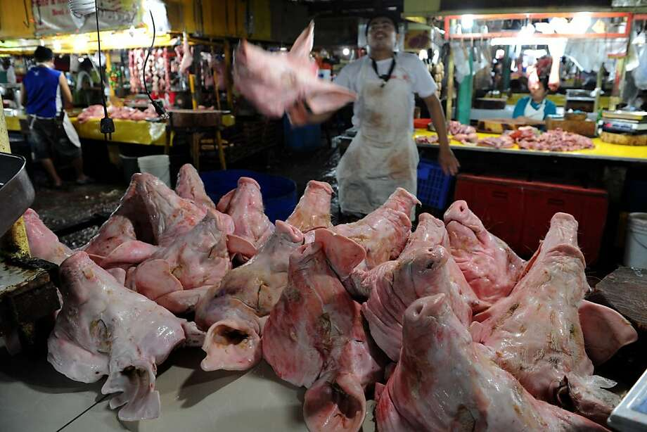 A butcher selling pig heads at a market looks on in Manila on January 4, 2013. The Philippines' inflation rate fell to a five-year low last year, the government said Friday, helping efforts to hold down interest rates and boost economic growth. Consumer prices expanded by 3.2 percent for the entire 2012, substantially lower than the 4.6 percent recorded in 2011, the National Statistics Office said.  Photo: Jay Directo, AFP/Getty Images