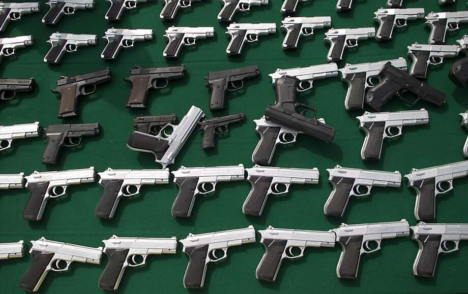 Realistic looking toy handguns that were seized by authorities for not meeting the requirement that toy guns are to be transparent or made of brightly colored plastic are displayed for the press at a government ceremony in Mexico City, Friday, Jan. 4, 2013. Mexico City authorities say they have destroyed thousands of toy guns in an effort to fight real crimes committed with fake weapons. The guns were confiscated from shops in Mexico City and the surrounding state of Mexico ahead of Three Kings Day on Sunday, when Mexican children receive the largest number of holiday gifts. Photo: Alexandre Meneghini, Associated Press