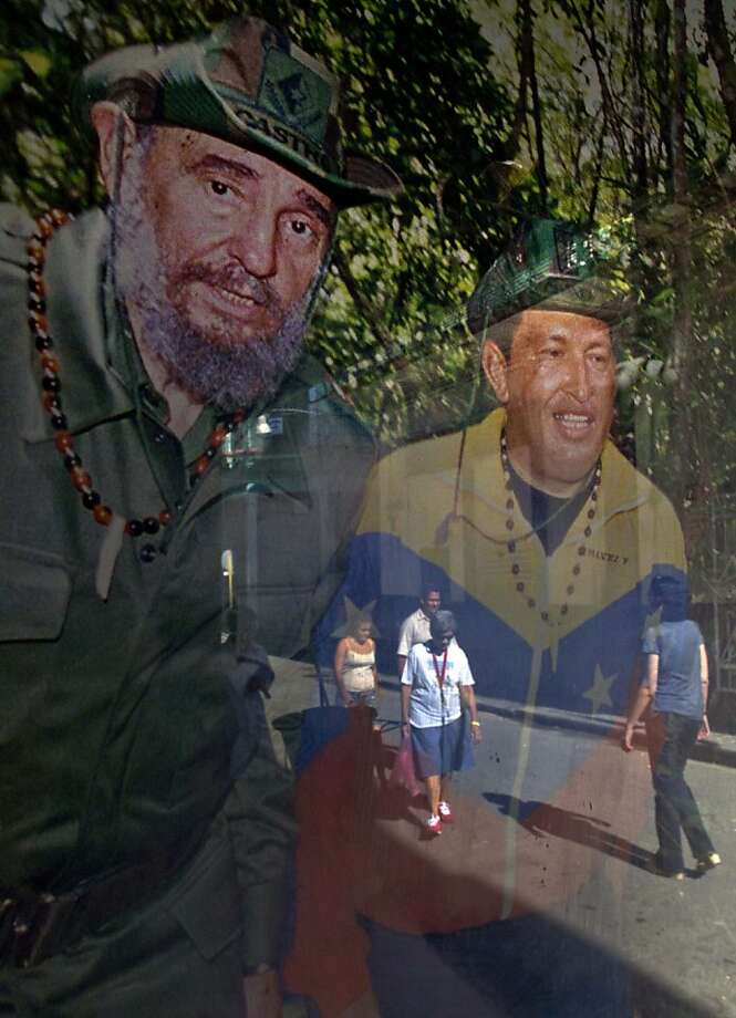 Pedestrians are reflected in a framed image of Cuba's Fidel Castro, left, and Venezuela's President Hugo Chavez, hanging inside a shop, in Havana, Cuba, Friday, Jan. 4, 2013. Chavez hasn't spoken publicly or been seen since his Dec. 11 operation in Cuba, and the latest report from his government Thursday night increased speculation that he is unlikely to attend his Jan. 10 inaugural ceremony. Photo: Ramon Espinosa, Associated Press